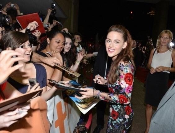 A atriz Kristen Stewart distribui autógrafos para fãs antes da exibição de