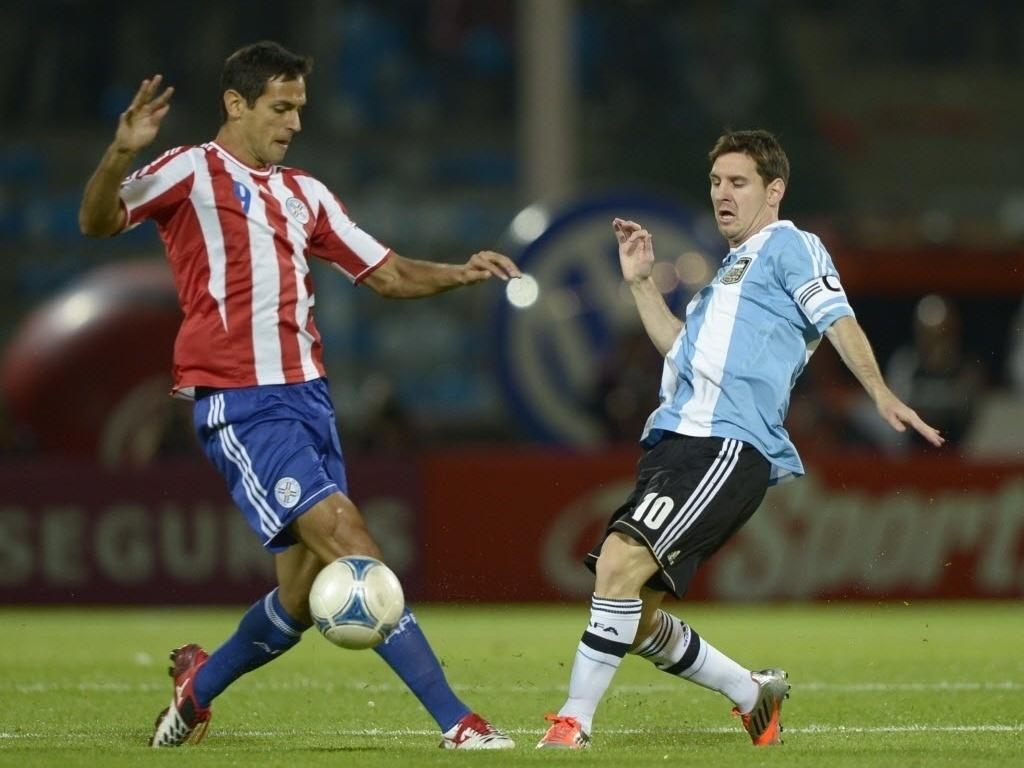 Lionel Messi (dir.) disputa a posse da bola com Roque Santa Cruz na partida entre Argentina e Paraguai