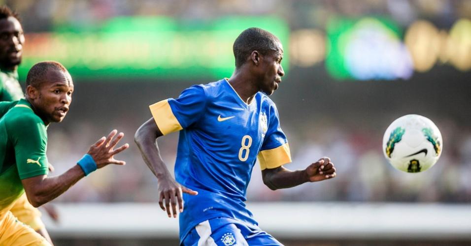 Observado por dois sul-africanos, Ramires tenta a jogada durante amistoso da seleção