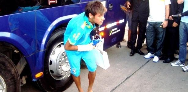 Neymar se abaixa para pegar os presentes atirados pelos fãs da seleção na porta do hotel em Recife