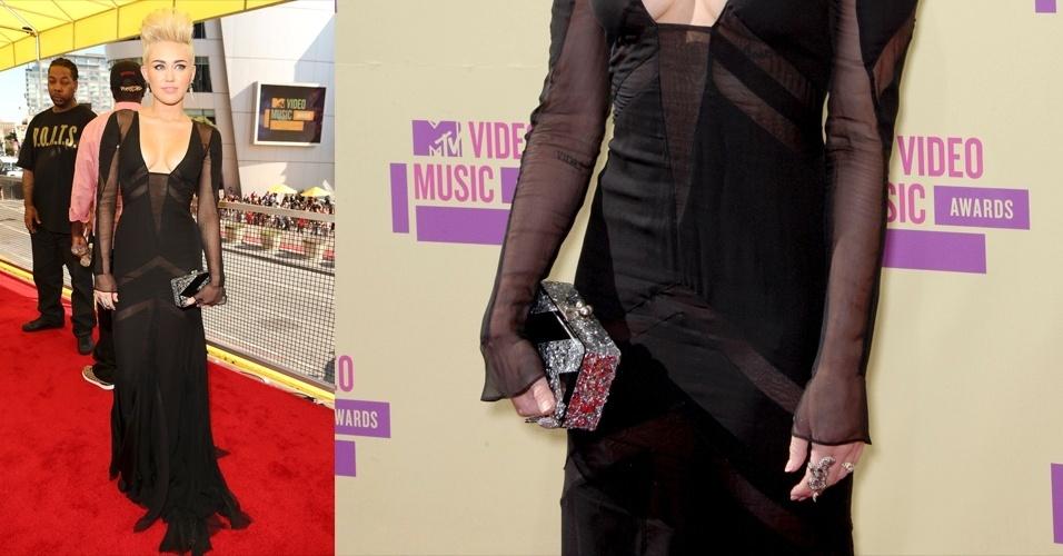 Para complementar seu look gótico, Miley Cyrus escolheu uma cluch Edie Parker prata brilhante com desenhos em preto