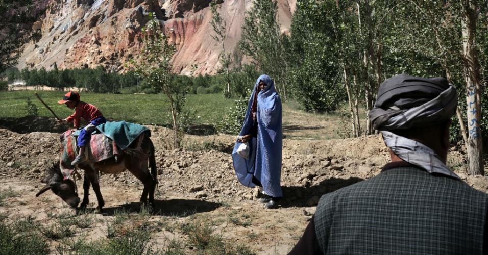 """11.set.2012  - Menino anda em cima de burro próximo a concessão Hajigak em Bamiyan, no Afeganistão, enquanto seus pais o observam. Ainda que o país tenha cerca de US$ 1 trilhão em recursos naturais - incluindo petróleo, ouro e cobre - para ser explorado, os afegãos dizem que a """"esperança de autossuficiência é temperada por preocupações sobre a corrupção e a segurança"""""""
