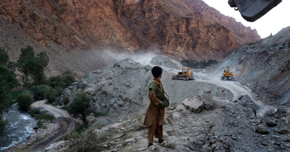 """11.set.2012 - Menino observa a construção de uma estrada no vale do Kalu, em Bamiyan, no Afeganistão, região que tem grandes depósitos de minério de ferro. Ainda que o país tenha cerca de US$ 1 trilhão em recursos naturais - incluindo petróleo, ouro e cobre - para ser explorado, os afegãos dizem que a """"esperança de autossuficiência é temperada por preocupações sobre a corrupção e a segurança"""""""