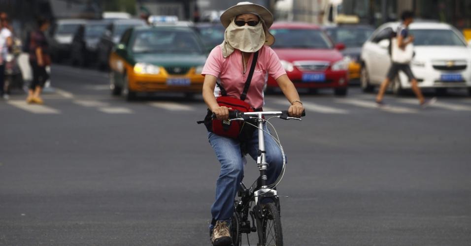 11.set.2012 - Mulher anda de bicileta usando máscara para se proteger da poluição em Pequim, na China