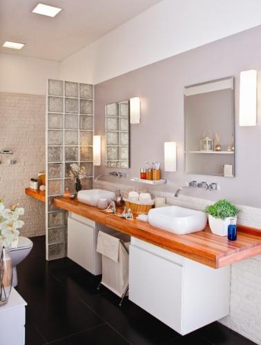 O banheiro do casal explora as texturas visuais e a combinação de revestimentos foscos e com brilho. Os tons neutros dão um contraste com o piso preto fosco. A casa projetada pelo arquiteto Gustavo Calazans está em exposição na 1ª Mostra Casa Leroy Merlin, em São Paulo