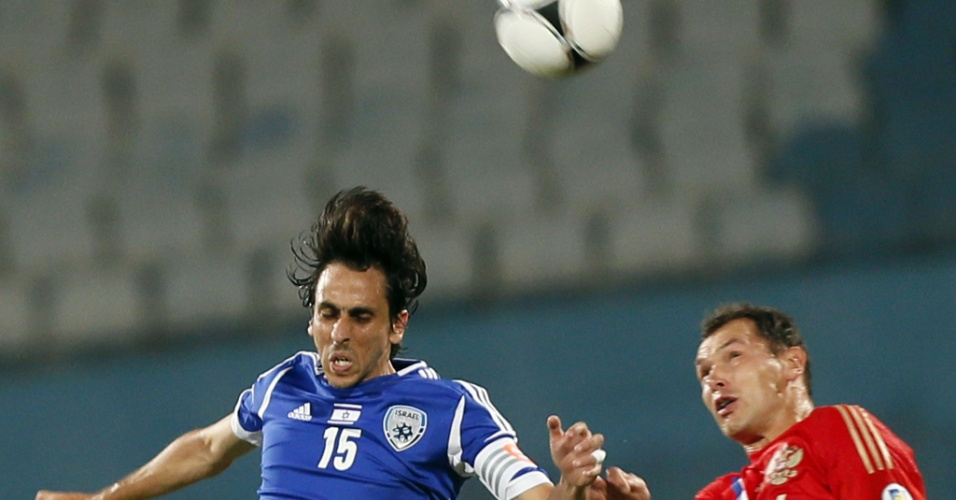 O capit&#227;o de Israel Yossi Benayoun, ex-Chelsea, Arsenal e Liverpool, sobe para cabecear bola ao lado do russo Sergei Ignashevich