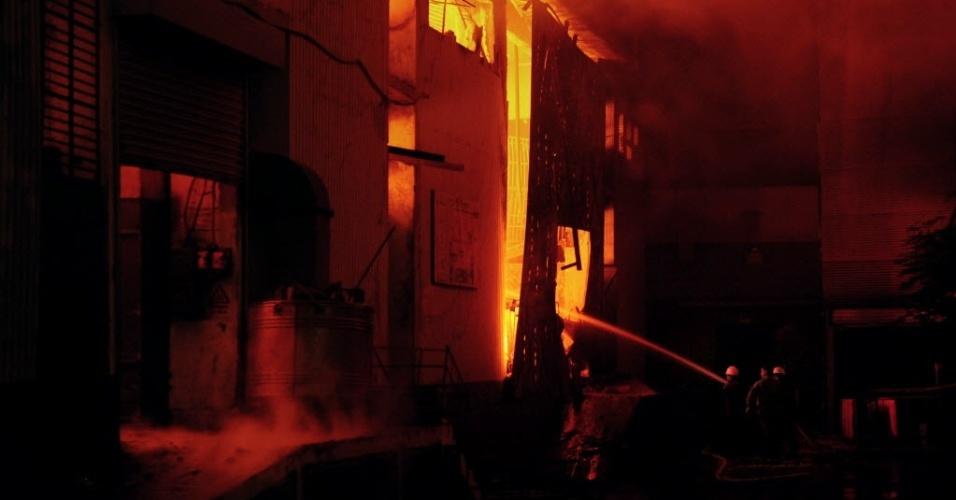 12.set.2012 - Bombeiros tentam apagar incêndio que atingiu fábrica de tecidos em Karachi, no Paquistão, nesta quarta-feira (12). Pelo menos 63 pessoas morreram