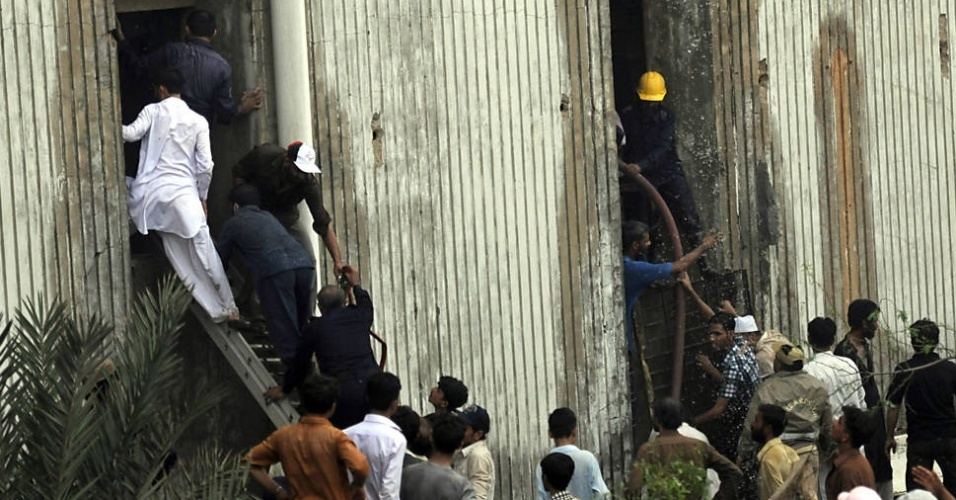 12.set.2012 - Equipes de resgate paquistanesas vítimas de incêndio em fábrica de tecidos em Karachi. Pelo menos 310 pessoas morreram em dois incêndios no país. O primeiro, em uma fábrica de sapatos de Lahore deixou 21 mortos. O segundo, na fábrica têxtil de Karachi, deixou 289 mortos, segundo a AFP