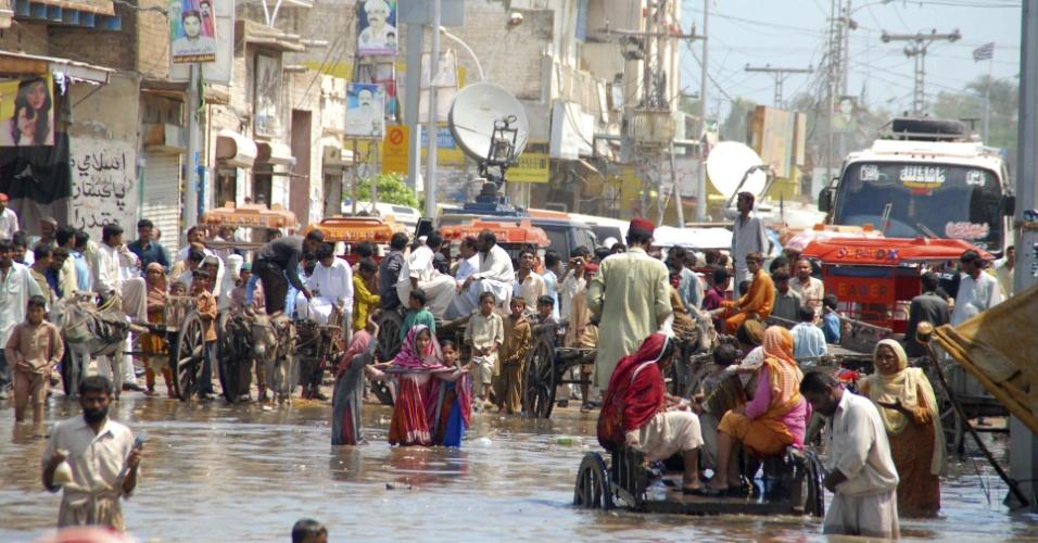 12.set.2012 - Pessoas passam por rua inundada nesta quarta-feira (12) em Shikarpur, na província paquistanesa de Sindh. As chuvas de monções deixaram ao menos 80 mortos e centenas de desalojados no Paquistão