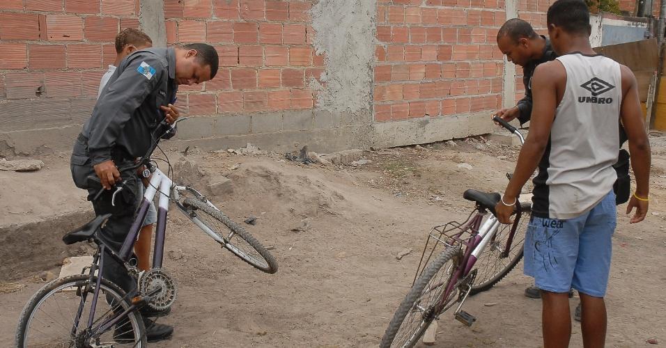 12.set.2012 - Policiais revistam garotos que voltam da mata, perto da favela da Chatuba, na Baixada Fluminense, onde teria ocorrido a chacina que vitimou seis jovens no último fim de semana
