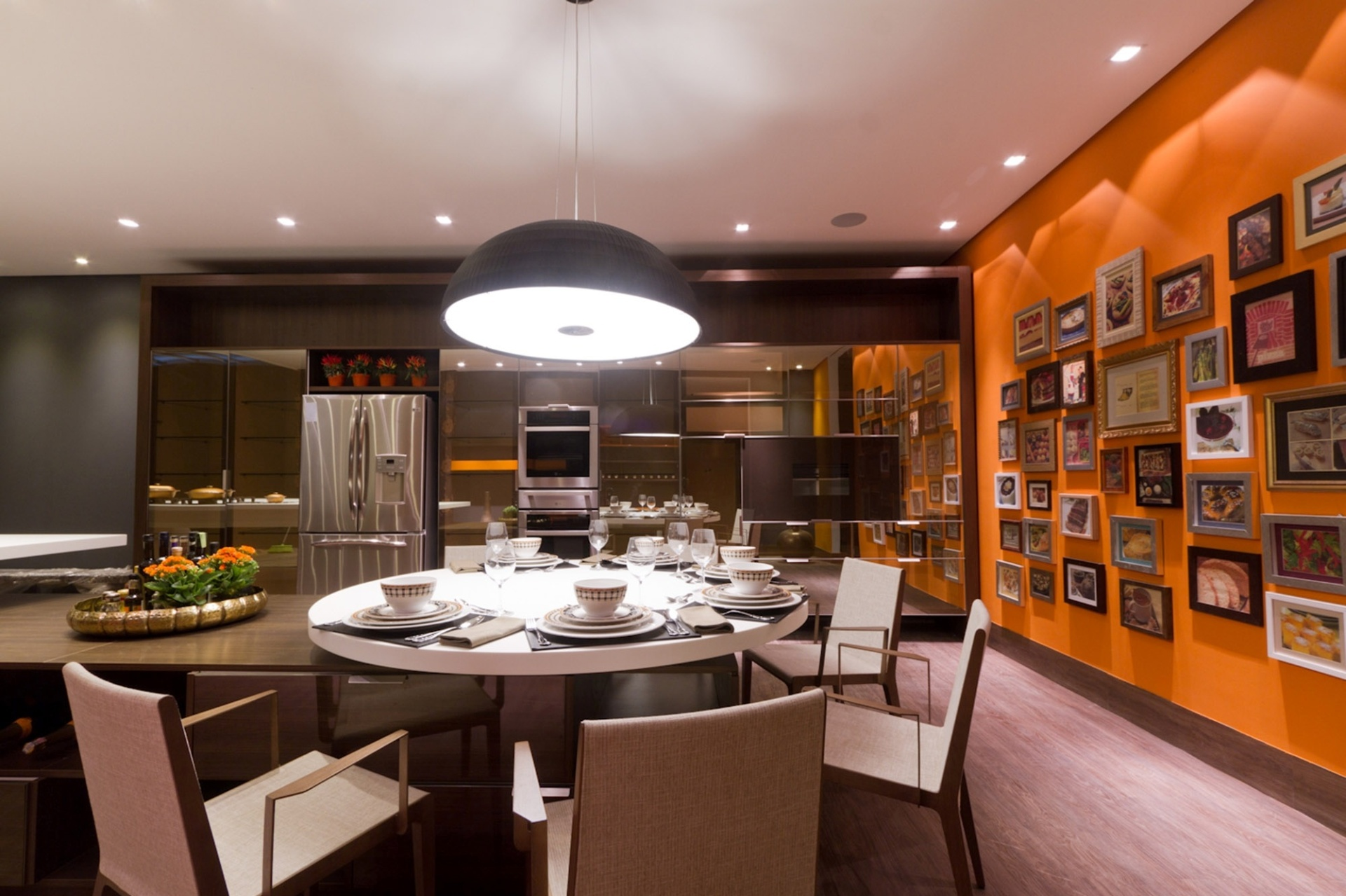 Casa Cor MT - 2012: a Cozinha criada pela arquiteta Tanise Tonin tem uma de suas paredes pintada com um laranja intenso. Na superfície, uma série de quadros com temática culinária dá personalidade ao espaço