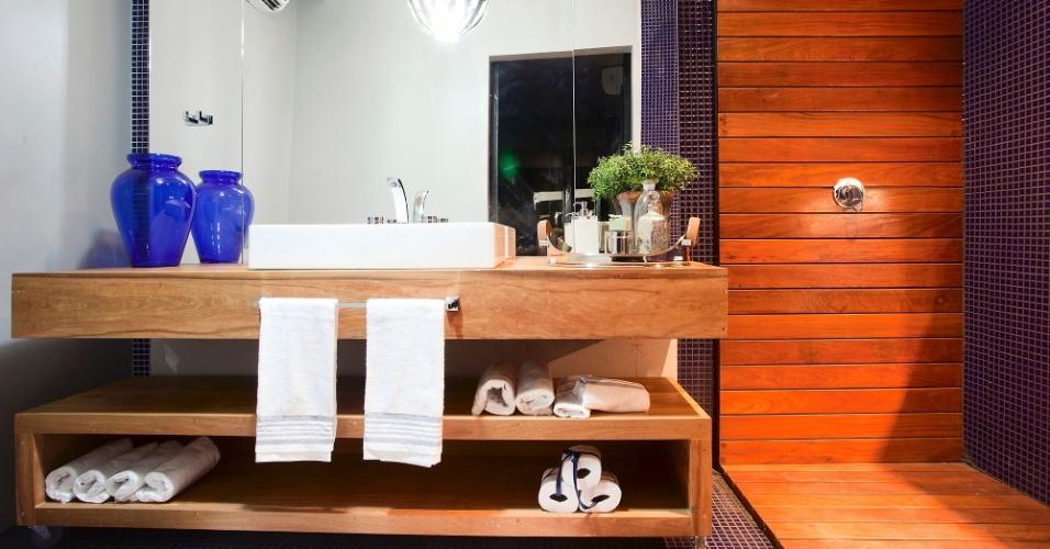 Casa Cor MT - 2012: o Banho do Rapaz é assinado pela arquiteta Marina Orsatto Riva e pelos designers Cibele Morais Koehler e Manoel Pereira da Silva Filho. No revestimento das paredes, a pintura tradicional é combinada às pastilhas cerâmicas de azul intenso e painéis de madeira, ambos com continuidade para o piso