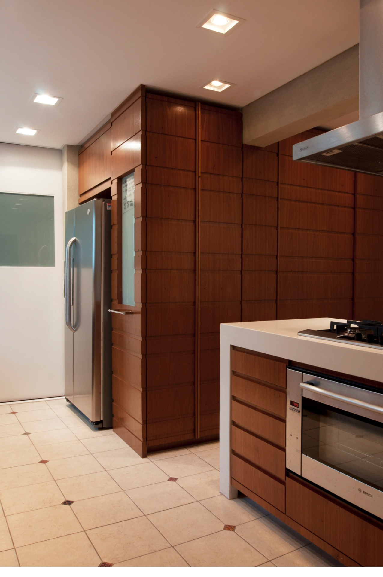 A caixa em madeira freijó avança para dentro da cozinha e oferece um nicho para a geladeira. A porta branca com vidro, também de correr, leva à futura brinquedoteca. Quando as crianças forem maiores, poderão brincar sob os olhos atentos dos pais. No piso da cozinha do apartamento Itapaiuna II, projetado por Crisa Santos, cerâmica Eliane