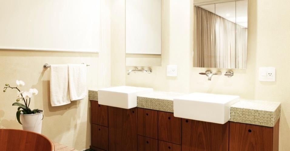 No banheiro do casal, os espelhos fixos ao trilho são, na verdade, portas de correr para nichos escondidos na parede. Pastilhas Vidrotil, madeira freijó (Mobília Brasil), metais Docol e louças Deca compõem o espaço projetado por Crisa Santos para o apartamento Itapaiuna II
