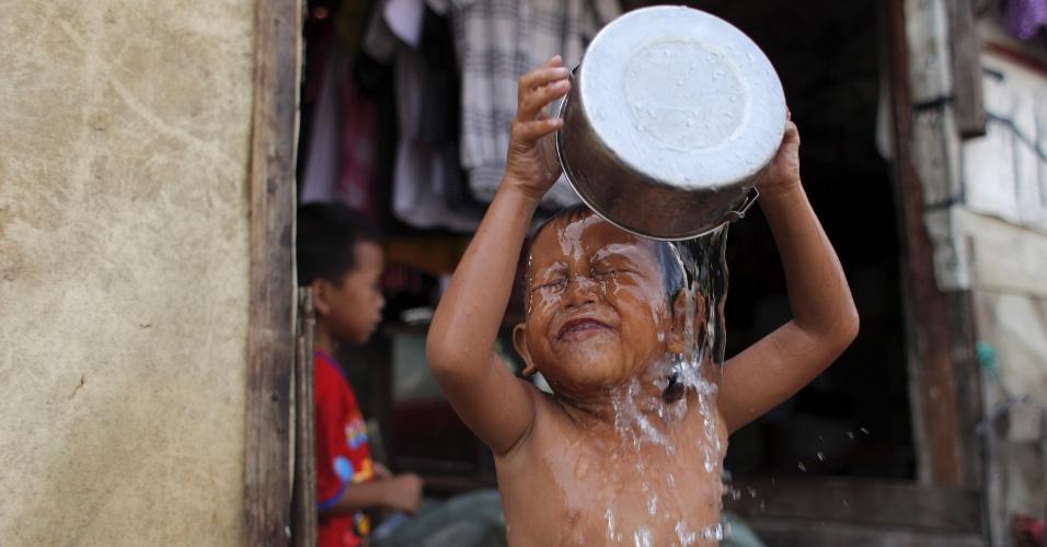 14.set.2012 - Criança joga água na cabeça em favela de Jacarta, na Indonésia