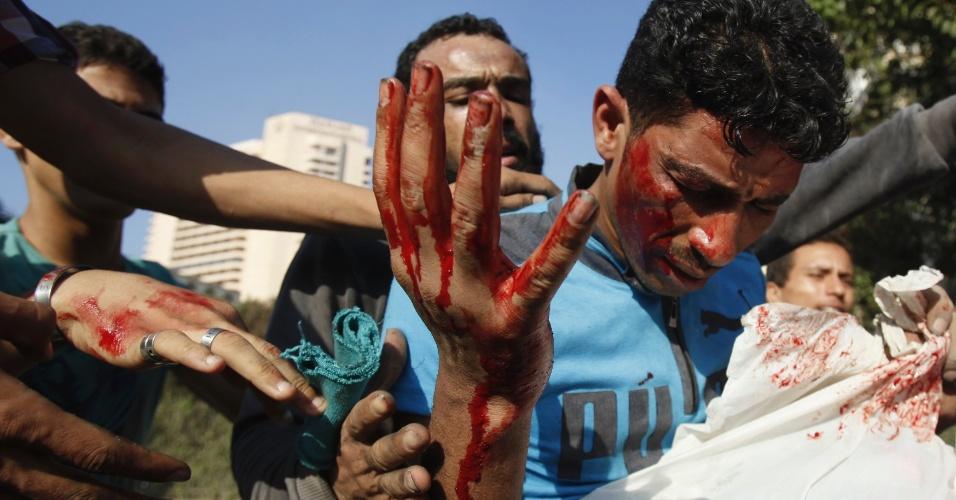 14.set.2012 - Manifestantes ajudam homem ferido durante conflitos nesta sexta-feira (14), perto da rpaça Tahir, no Cairo, capital do Egito, no caminho para a embaixada dos Estados Unidos no país. Egípcios protestam contra um filme americano que insuta o profeta Maomé e a polícia interviu para impedir que eles invadissem a embaixada