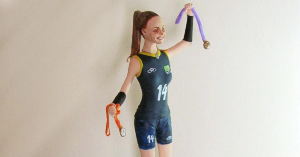 A boneca de Fabi está vestida com uniforme azul marinho e traz uma medalha de ouro em casa mão (a de Pequim-2008 e a de Londres-2012)