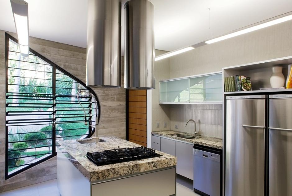 A cozinha reúne a modernidade do aço escovado dos eletrodomésticos e a nobreza do mármore. Contudo, em relação aos demais cômodas da Casa Valinhos, o espaço ganha destaque por um elemento em especial: a janela em formato arredondado que recebeu venezianas de vidro. O projeto é assinado por Ruy Ohtake