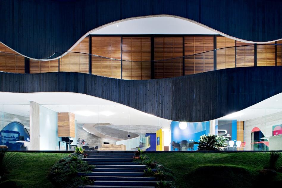 A vista noturna da residência iluminada cria um bonito efeito cênico. Destacam-se o paisagismo criado pelo escritório Burle Marx, a piscina e a sinuosidade do traçado curvilíneo da Casa Valinhos, assinada por Ruy Ohtake