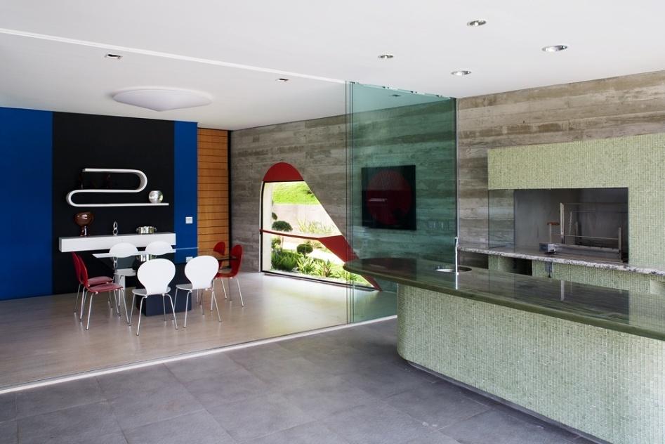 As salas de almoço e jantar e a churrasqueira, todas integradas, são delimitadas apenas por portas de vidro. A saleta de almoço tem parede azul e preta que apoia prateleira curva e aparador, ambos desenhados por Ruy Ohtake - que também assina a arquitetura da Casa Valinhos - e executados por Oscar Kusaka. Em volta da mesa de almoço foram combinadas cadeiras brancas e vermelhas