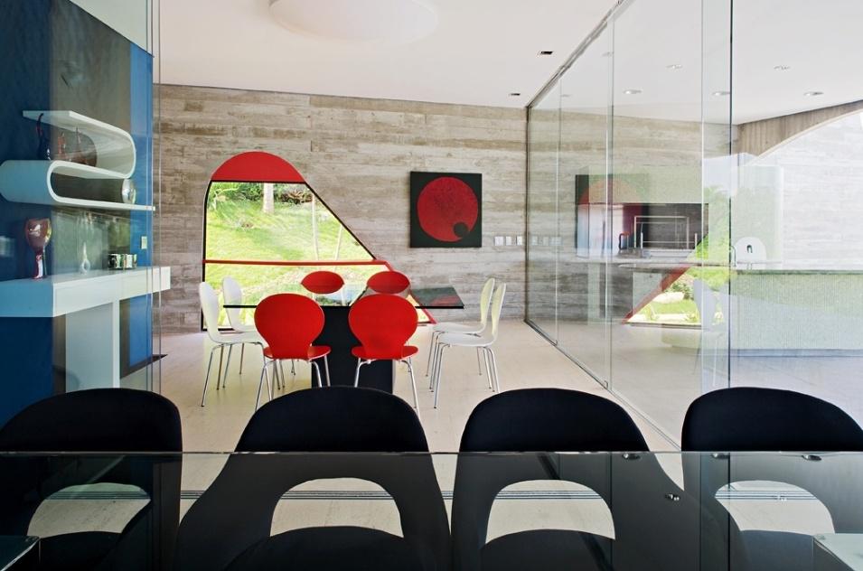 As salas de almoço e jantar e a churrasqueira, todas integradas, são delimitadas apenas por portas de vidro de correr. A saleta de almoço tem parede azul e preta que apoia prateleira curva e aparador, ambos desenhados por Ruy Ohtake - que também assina a arquitetura da Casa Valinhos - e executados por Oscar Kusaka. A mesa de jantar (em primeiro plano), criada pelo arquiteto é de vidro e concreto e cadeiras são Charles Eames