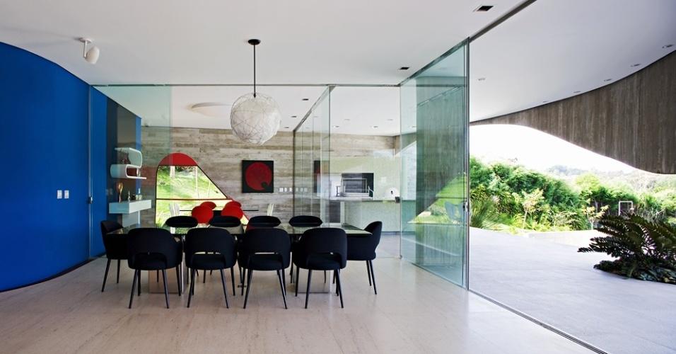 As salas de almoço e jantar e a churrasqueira, todas integradas, são delimitadas apenas por portas de vidro de correr. A saleta de almoço tem parede azul e preta que apoia prateleira curva e aparador, ambos desenhados por Ruy Ohtake - que também assina a arquitetura da Casa Valinhos - e executados por Oscar Kusaka. A mesa de jantar, criada pelo arquiteto é de vidro e concreto e cadeiras são Charles Eames