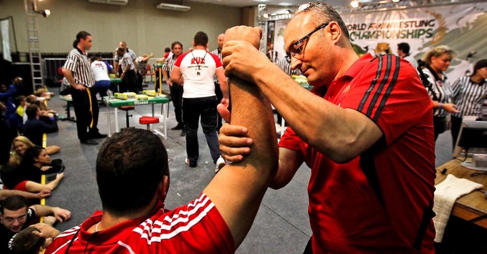 Atleta realiza alongamento antes de competir no Mundial de Luta de Braço em São Vicente