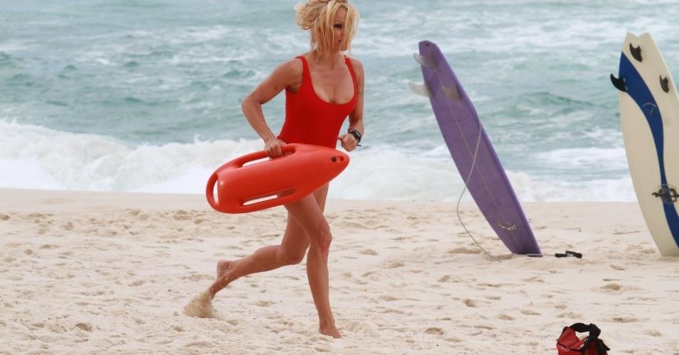 """Com maiô vermelho, igual ao que usava em """"SOS Malibu"""", a atriz Pamela Anderson gravou um comercial em praia do Rio de Janeiro (14/9/12)"""