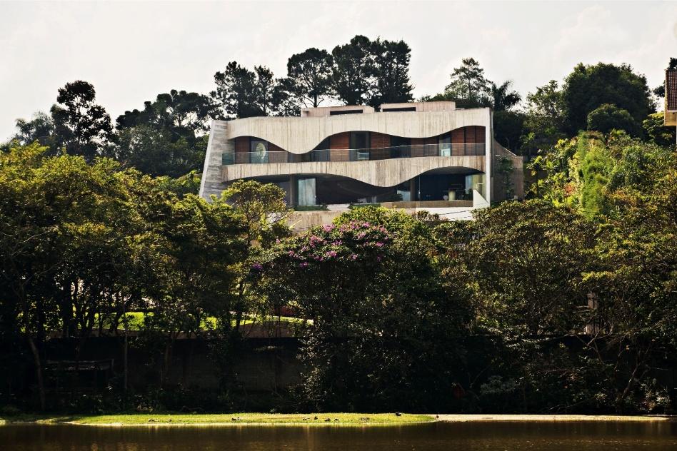 Envolta pelo verde das árvores e gramados planejados pelo escritório Burle Marx, a Casa Valinhos se sobressai de forma cinematográfica. O projeto, com seu concreto aparente e curvas sinuosas, é assinado pelo arquiteto Ruy Ohtake