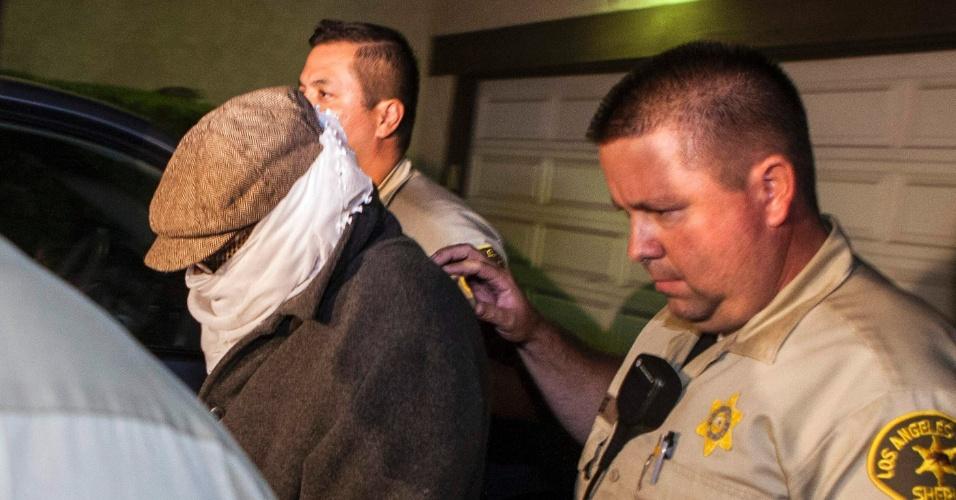 15.set.2012 - Homem não-identificado é escoltado pela polícia para fora da residência de Nakoula Basseley Nakoula, neste sábado (15), em Los Angeles (EUA)