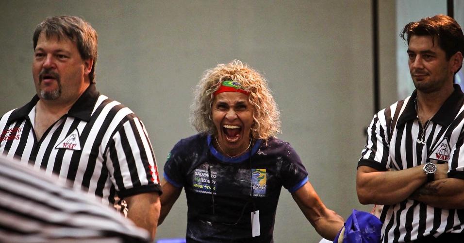 Brasileira Chris Regiane comemora uma de suas vitórias no Mundial de Luta de Braço; ela disputa entre as masters, por ter 50 anos, as deficientes, por ser surda de um ouvido, e no adulto
