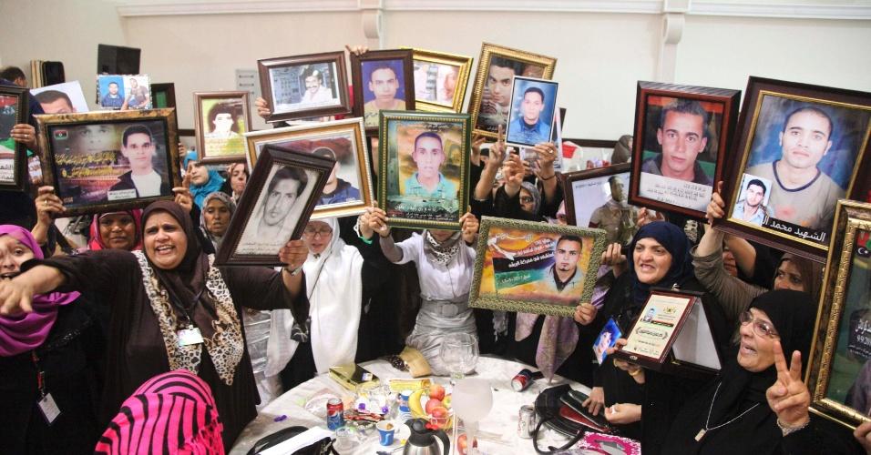 16.set.2012 - Mães mostram fotos dos filhos mortos ao longo do último ano, neste domingo (16), dia dos mártires, em Benghazi, na Líbia. Durante quase todo o ano de 2011, o país viveu um clima de guerra devido aos confrontos entre opositores e forças de segurança do ex-presidente Muammar Gaddafi, morto em outubro pelos rebeldes, após mais de 40 anos à frente do poder