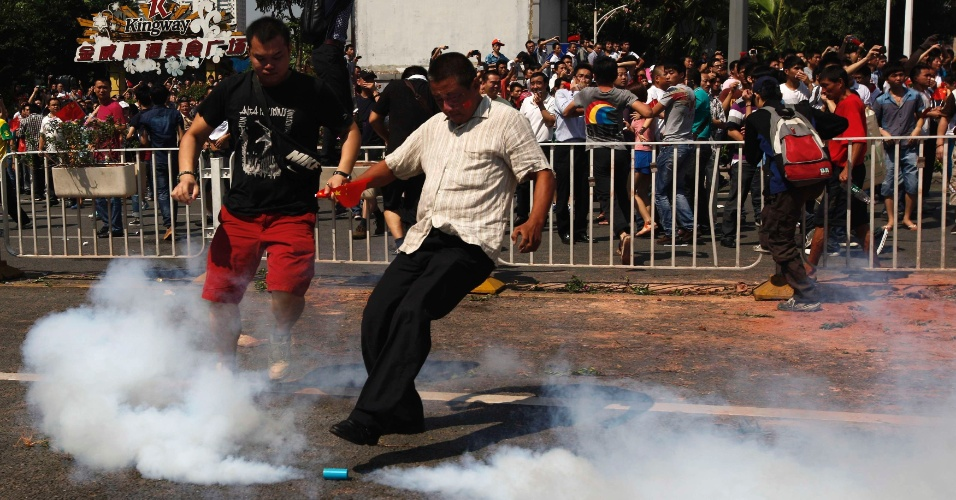 16.set.2012 - Manifestante chuta uma bomba de gás lacrimogêneo lançada pela polícia durante protesto neste domingo (6) em Pequim (China)