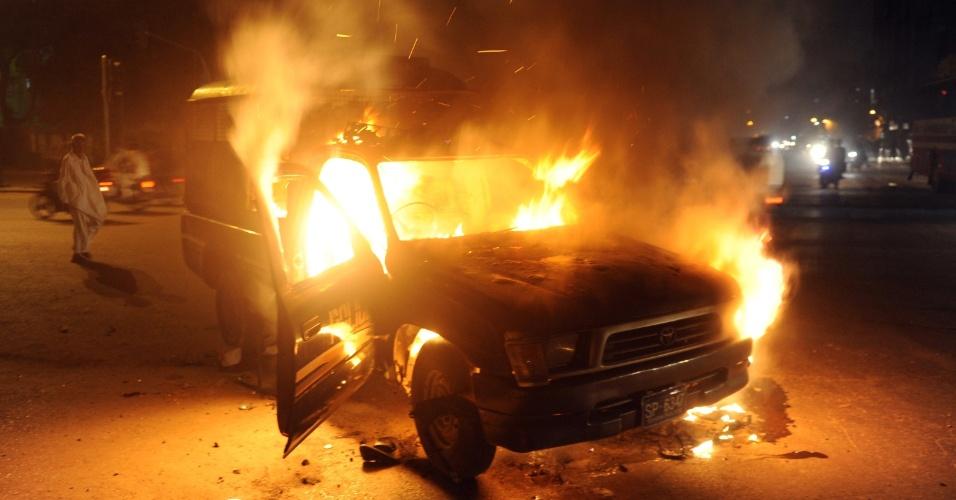 16.set.2012 - Muçulmanos xiitas ateiam foto em um carro da polícia, em Karachi, no Paquistão, em protesto contra um filme anti-islã feito nos Estados Unidos