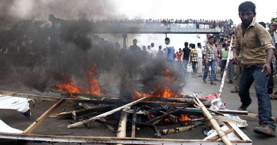 16.set.2012 - Trabalhadores da indústria de vestuário ateiam fogo em placas de rua durante confronto com a polícia em Narayanganj, em Bangladesh