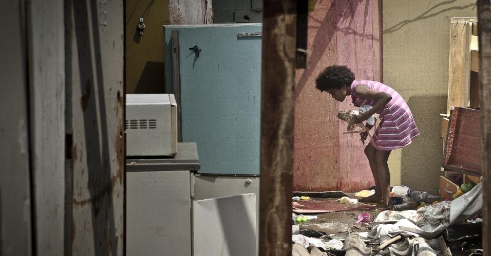 17.ago.2012 - Criança procura brinquedos  em meio aos escombros do incêndio que atingiu a favela do Moinho, região central de São Paulo, na manhã desta segunda-feira (17). Ao menos uma pessoa morreu e cerca de 50 famílias ficaram desabrigadas. Segundo a polícia, o suspeito de iniciar o fogo na comunidade foi preso e é acusado de ter trancado o parceiro em um barraco em chamas após uma briga