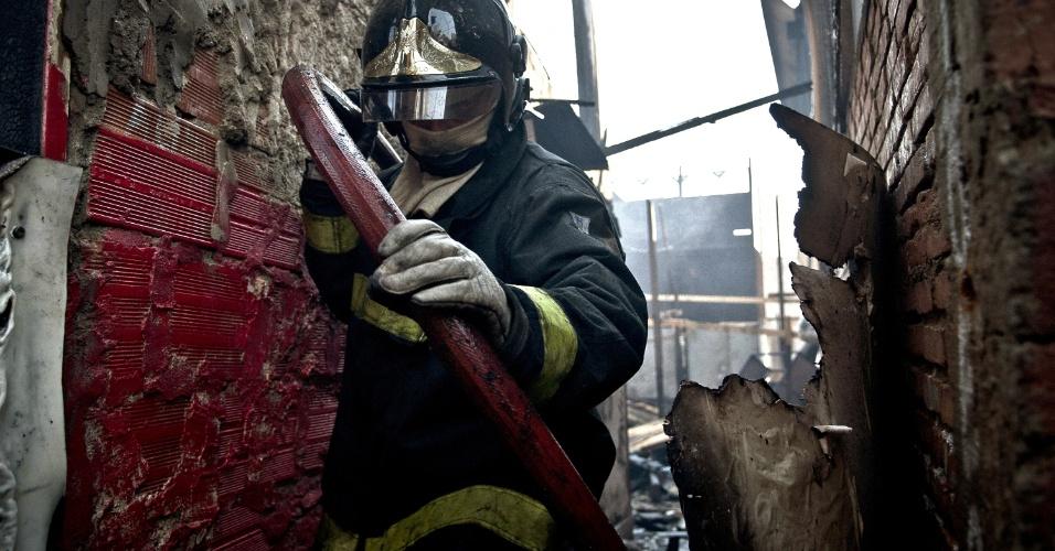 17.set.2012 - Bombeiro caminha em meios aos escombros do incêndio que atingiu a favela do Moinho, região central de São Paulo, na manhã desta segunda-feira (17). Ao menos uma pessoa morreu e cerca de 50 famílias ficaram desabrigadas. Segundo a polícia, o suspeito de iniciar o fogo na comunidade foi preso e é acusado de ter trancado o parceiro em um barraco em chamas após uma briga