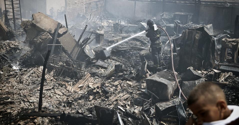 17.set.2012 - Bombeiro tenta conter incêndio que atingiu a favela do Moinho, região central de São Paulo, na manhã desta segunda-feira (17). Ao menos uma pessoa morreu e cerca de 50 famílias ficaram desabrigadas. Segundo a polícia, o suspeito de iniciar o fogo na comunidade foi preso e é acusado de ter trancado o parceiro em um barraco em chamas após uma briga