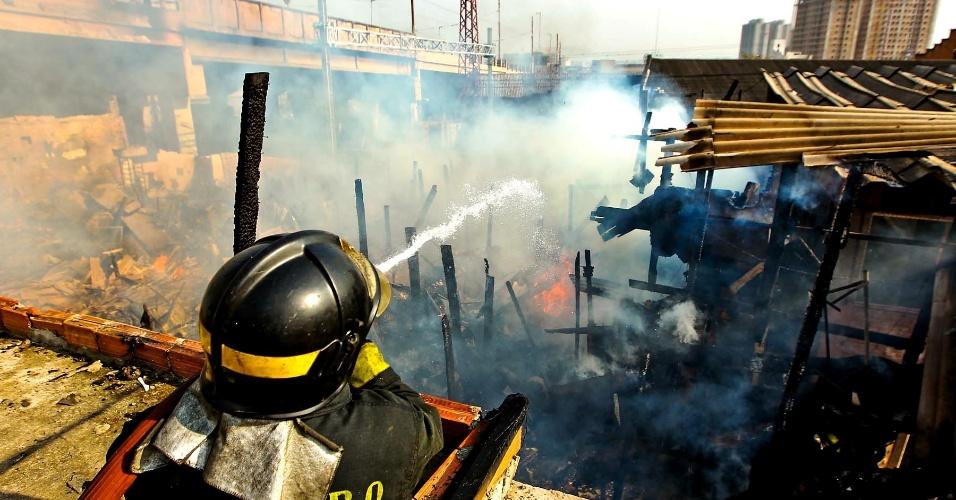 17.set.2012 - Bombeiros trabalham para apagar o fogo que atingiu a favela do Moinho, em São Paulo, nesta segunda-feira (17). O fogo foi controlado às 8h30, e uma pessoa morreu