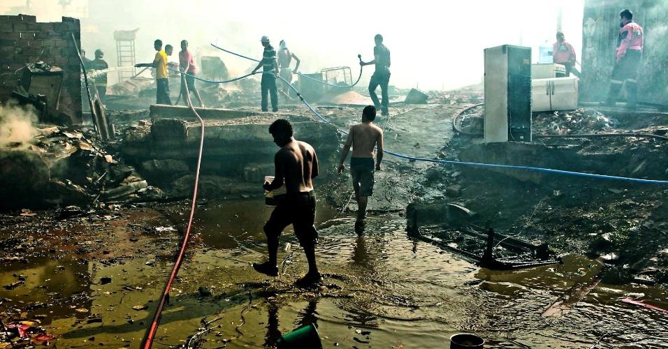 17.set.2012 - Moradores da favela do Moinho, em São Paulo, ajudam os bombeiros a eliminar os focos do incêndio que atingiu o local nesta segunda-feira (17). Segundo a Defesa Civil, 80 barracos foram danificados. Os bombeiros confirmara a morte de uma pessoa