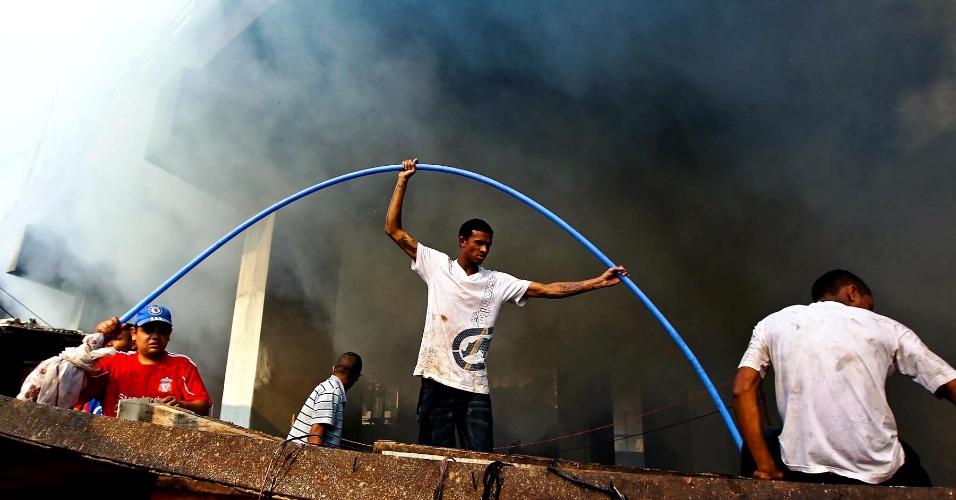 17.set.2012 - Moradores da favela do Moinho, em São Paulo, tentam apagar o incêndio que atingiu o local na manhã desta segunda-feira (17)