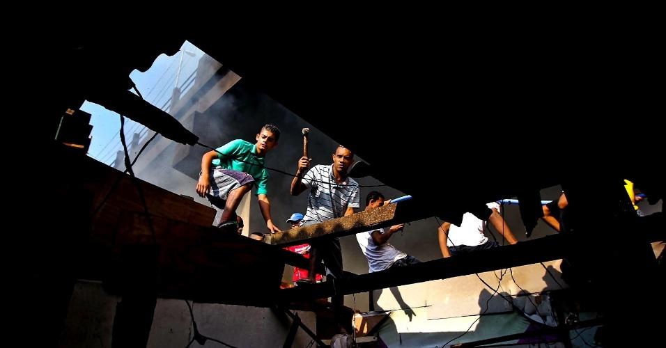 17.set.2012 - Moradores entram em barraco da favela do Moinho, em São Paulo, para retirar pertences após o incêndio que atingiu o local na manhã desta segunda-feira (17). O fogo foi controlado às 8h30, e uma pessoa morreu, segundo os bombeiros