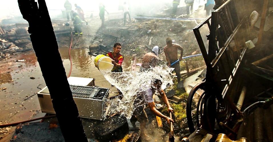 17.set.2012 - Moradores usam balde para apagar foco de incêndio na favela do Moinho, em São Paulo, nesta segunda-feira (17). Segundo a Defesa Civil, 80 barracos foram danificados