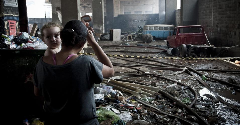 17.set.2012 - Mulher com criança no colo observa estragos do incêndio que atingiu a favela do Moinho, região central de São Paulo, na manhã desta segunda-feira (17). Ao menos uma pessoa morreu e cerca de 50 famílias ficaram desabrigadas. Segundo a polícia, o suspeito de iniciar o fogo na comunidade foi preso e é acusado de ter trancado o parceiro em um barraco em chamas após uma briga