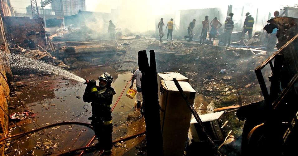 17.set.2012 -Bombeiro apaga foco de incêndio na favela do Moinho, em São Paulo, nesta segunda-feira (17). Ao lado, um fogão e duas geladeiras danificados