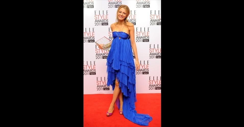 """Blake Lively usou um vestido tomara que caia azul com muitas camadas plissadas e uma discreta cauda. O look colorido da atriz de """"Gossip Girl"""" contou com sapatos peep toe roxo"""