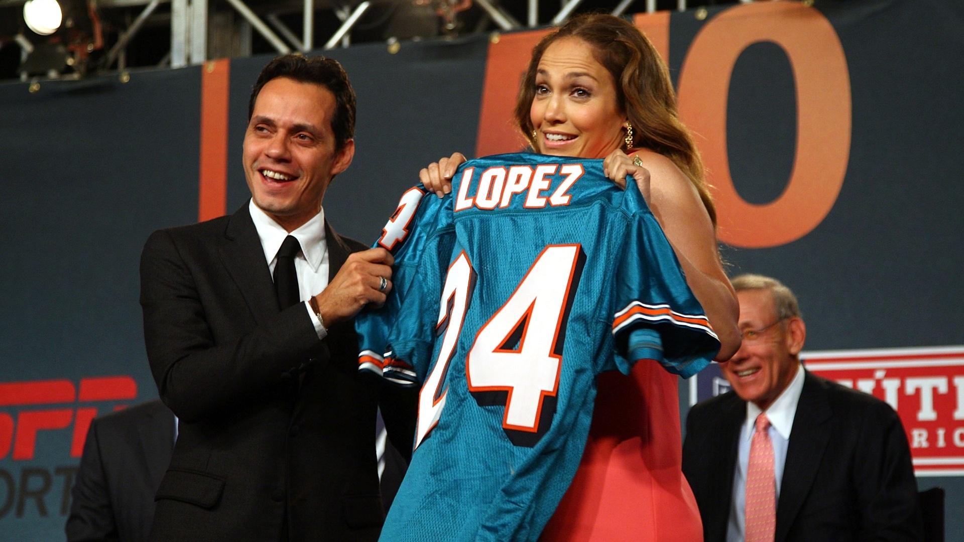 Cantores Marc Anthony (e) e Jennifer Lopez mostram camisa do Miami Dolphins, clube de futebol americano do qual são sócios