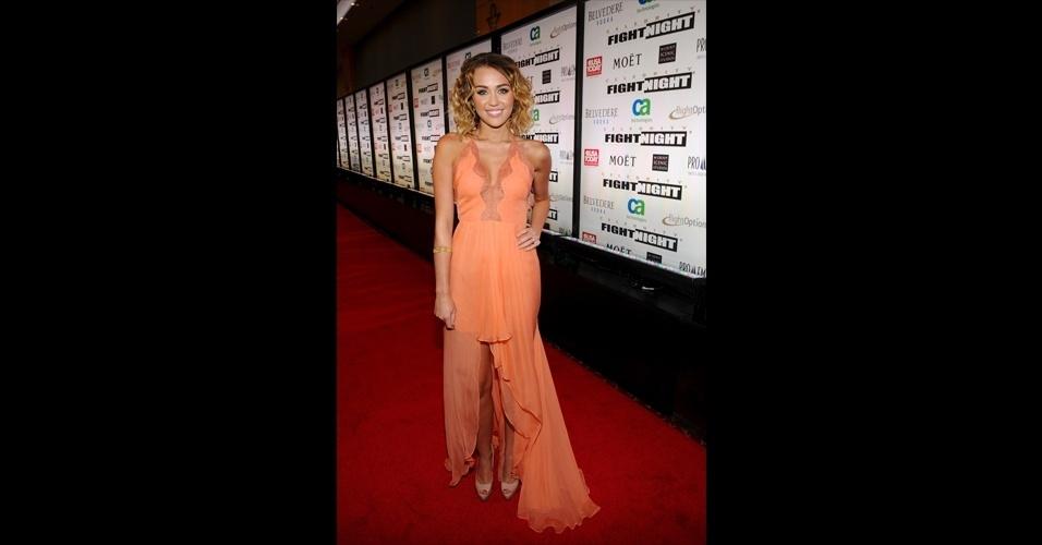 Miley Cyrus usou um vestido coral com saia mullet assimétrica que formava uma pequena cauda. Para alongar as pernas, a atriz usou sapatos de salto nude