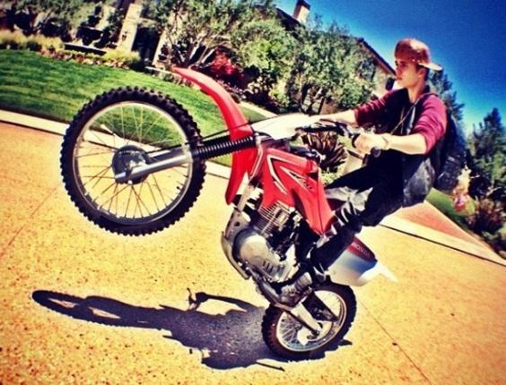 """O cantor canadense Justin Bieber publicou uma foto no Instagram nesta segunda-feira (17) na qual aparece empinando uma moto. Na legenda da imagem, o cantor escreveu """"não brinque"""", em alusão ao perigo da manobra que realizou com o veículo de duas rodas (17/9/12)"""