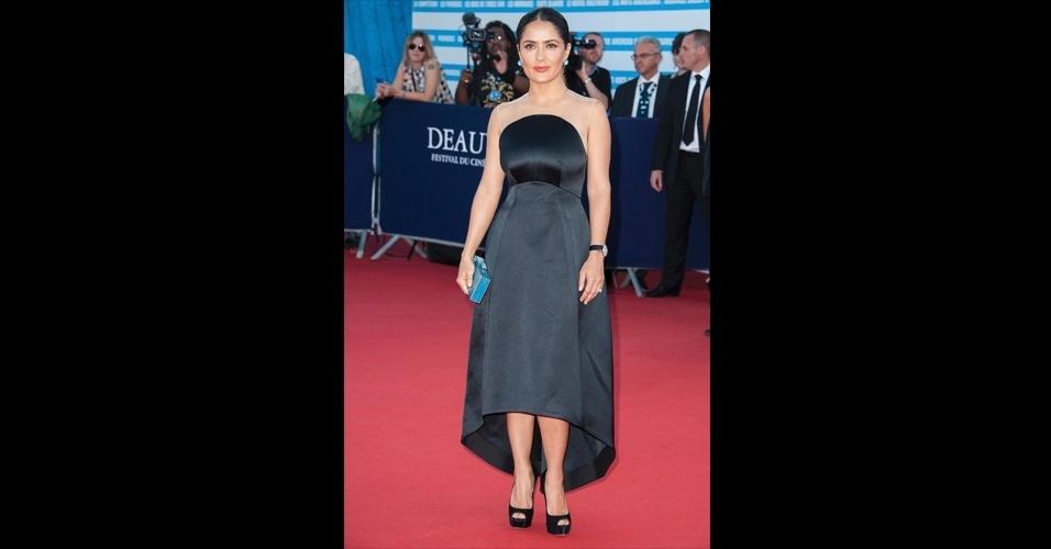O vestido preto Stella McCartney usado por Salma Hayek é estruturado e possui um desenho arredondado, o que acabou desvalorizando o corpo da atriz